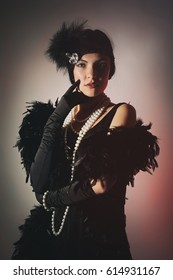 Portrait of beautiful woman in boa from ostrich feathers and pearls beads. 20's years.