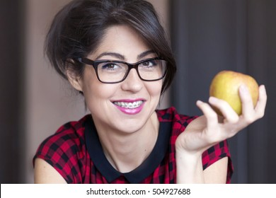 Portrait of a beautiful woman with braces on teeth eating green apple.Orthodontic Treatment. Dental care Concept
