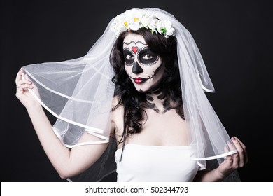 portrait of beautiful woman bride with creative sugar skull make up and bridal veil over black background