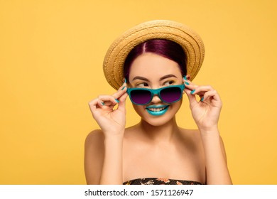 Portrait of beautiful woman with bright make-up, hat and sunglasses on yellow studio background. Stylish and fashionable make and hairstyle. Beauty, fashion and ad concept. Looking for, smiling.