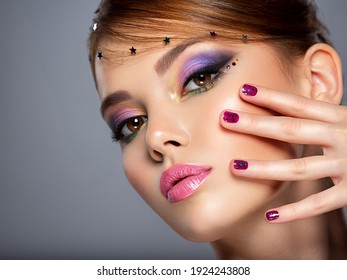 Portrait of a beautiful woman with bright makeup. Closeup female face with purple eye make-up. Pretty, sexy girl with violet nails near face. Stylish fashion model with a short slick hair