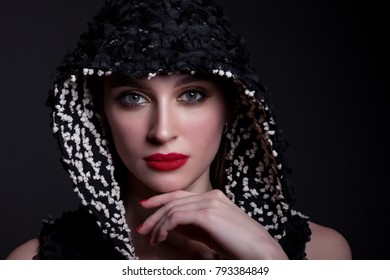 Portrait of a beautiful woman with bright make-up, red lipstick, on a black background and a hood on her head.
