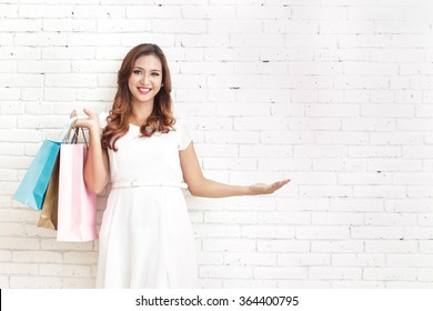 portrait of beautiful woman carrying shopping bags while presenting copy space with white brick wall on the background