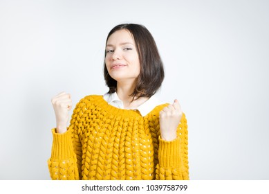portrait of a beautiful woman celebrating news with fists, isolated on gray background