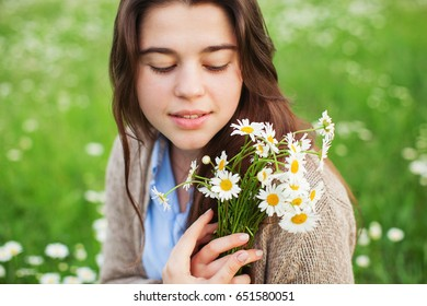 Portrait of beautiful woman with chamomile in nature.