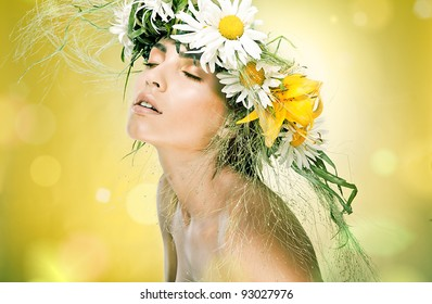 Portrait of beautiful woman with chaplet of flowers on yellow background