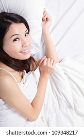 Portrait of beautiful Woman charming Smile face and she lying on the bed with white background, view from high angle, model is a asian girl