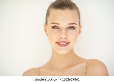 Portrait of beautiful woman with clean skin, youth concept, beauty treatment. Cheerful teen girl, beauty female face happy smiling and looking at camera over white background