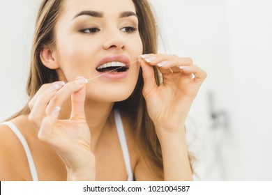 portrait of beautiful woman cleaning teeth with dental floss