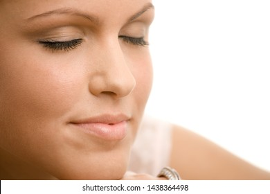 Portrait of beautiful woman with closed eyes, white background.