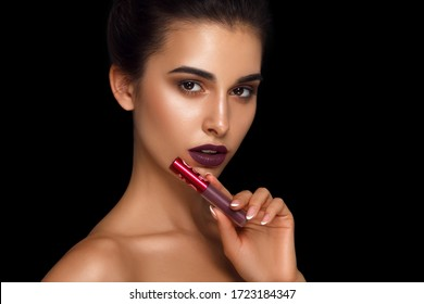 Portrait of beautiful woman close-up. beauty fashion girl holding a lipstick. Isolated on a black background. Advertising cosmetics and make-up. Matte lips