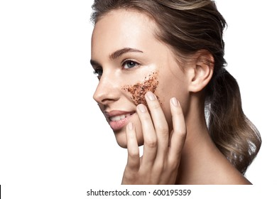 Portrait of a beautiful woman with a coffee scrub on her face doing peeling skin isolated on white background