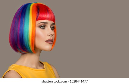Portrait of beautiful woman. Colorful hair. Gray background.
