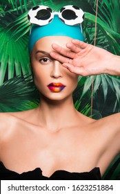 Portrait of beautiful woman with colorful make up, beauty magazine editorial ready, Caucasian girl, with swimming hat, sunglasses and tropical exotic background - Shutterstock ID 1623251884