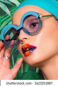 Portrait of beautiful woman with colorful make up, beauty magazine editorial ready, Caucasian girl, with swimming hat, sunglasses and tropical exotic background - Shutterstock ID 1623251887