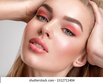Portrait of a beautiful woman with a coral color makeup. Attractive blonde  girl with  bright fashion make-up, posing at studio. Beautiful female face. Closeup portrait of pretty lady. Fashion model.