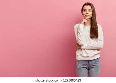 Portrait of beautiful woman crosses arm over waist, holds chin, looks left side, thinks about something, makes plans in mind, wears fashionable clothes, isolated over pink wall with blank space
