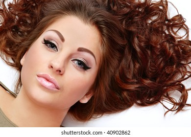 Portrait of beautiful woman with curly hair lying on white background