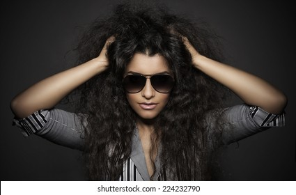 Portrait of beautiful woman with curly hairs and glasses, on dark background