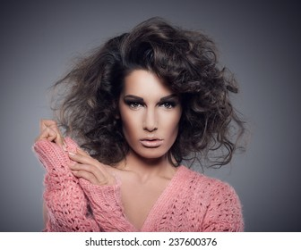 Portrait of beautiful woman with curly hairs and pink sweater, looking at camera