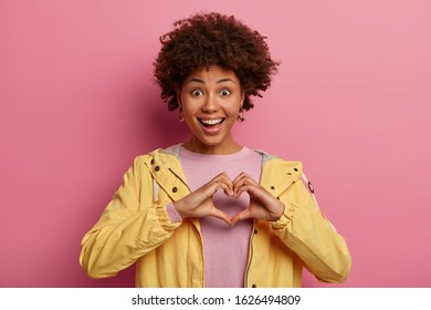 Portrait of beautiful woman with curly hairstyle makes heart gesture over chest, expresses love, says be my valentine, has positive expression, wears yellow anorak, adores boyfriend. Hand sign