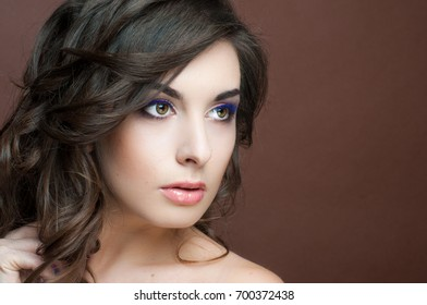Portrait of a beautiful woman with dark wavy hair, festive bridal make-up, fashion look, glowing healthy clean skin.