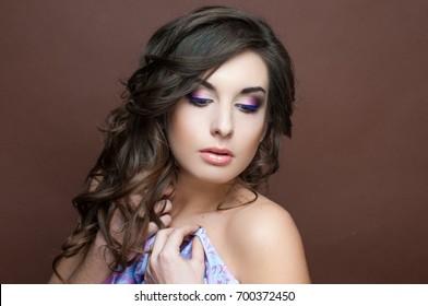 Portrait of a beautiful woman with dark wavy hair, festive bridal make-up, fashion look, glowing healthy clean skin.