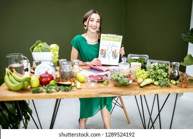 Portrait of a beautiful woman as a dietitian showing drawings on the topic of healthy food sitting with various healthy food ingredients indoors