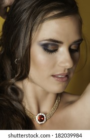 Portrait of beautiful woman with dramatic makeup and ruby and gold necklace