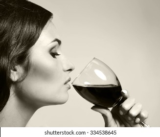 Portrait of beautiful woman drinking wine, black and white retro stylization