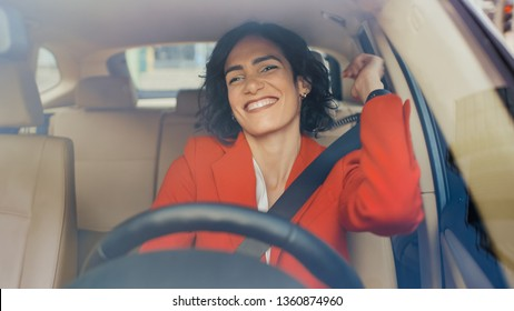 Portrait of Beautiful Woman Driving Car, Has Fun, Listens to Music. Camera Shot Made From the Front Windshield.