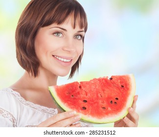 Portrait of beautiful woman eating fresh red ripe watermelon outdoors, tasty dessert of summer season, healthy nutrition