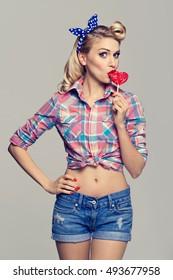 Portrait of beautiful woman eating heart shape lollipop, dressed in pin-up style dress in polka dot. Caucasian blond model posing in retro fashion and vintage concept studio shoot.