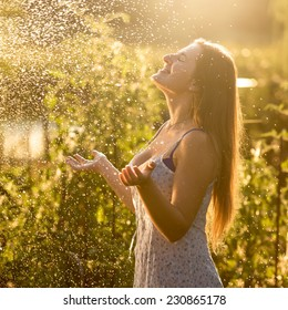Portrait of beautiful woman enjoying rain at sunny day at garden