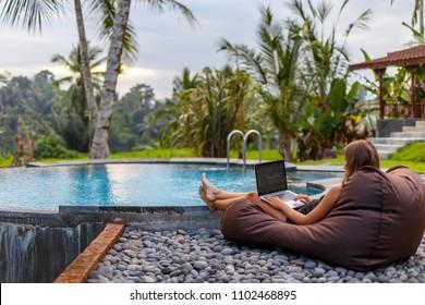 Portrait Beautiful woman enjoying relaxing edge pool typing on laptop, swimming pool blue water