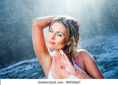 Portrait of beautiful woman enjoying of rest and harmony among sparkling water drops flying from river waterfalls in sunny summer  morning