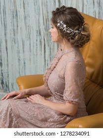 Portrait of beautiful woman in evening lace dress with makeup and hairstyle decorated by silver leaf shiny hair accessory