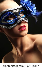 Portrait of beautiful woman with fancy glitter makeup and Masquerade mask on dark background