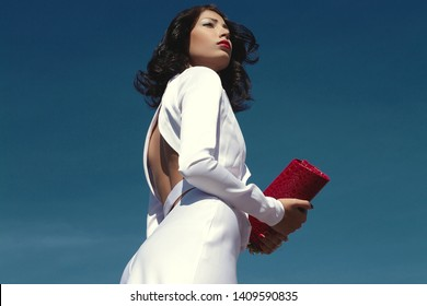 Portrait of beautiful woman (fashion model) posing in elegant white atlas cocktail dress with red clutch in her hands over blue sky background. Copy-space. Outdoor shot