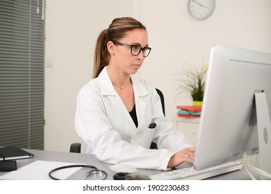 portrait of a beautiful woman female doctor in medical practice office working on computer