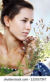 Portrait of beautiful woman with field plant in hands