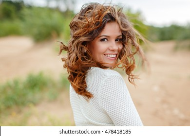 Portrait of a beautiful woman with flying hair in the wind, summer, closeup