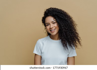 Portrait of beautiful woman with frizzy bushy hair, gentle smile and healthy skin, wears casual white t shirt, enjoys pleasant conversation stands against beige background copy space. People, emotions