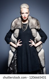 Portrait of a beautiful woman in a fur coat posing in a studio. Cool and strong. Fashion shot.