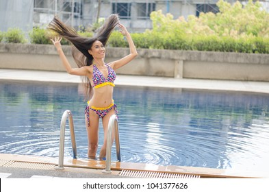 Portrait of a beautiful woman getting out of a swimming pool.Sexy girl in a bikini with thin and slim shape near the swimming pool.