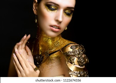 Portrait of Beautiful Woman with Golden Sparkles on her Face. Girl with Art Make-Up with Golden Sparkles. Fashion Model with Golden Makeup