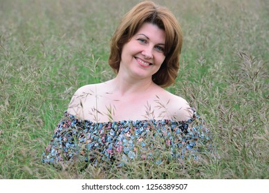 Portrait of beautiful woman in the grass on a summer day
