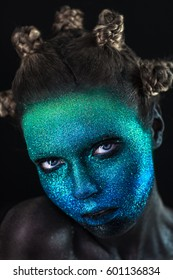 Portrait of beautiful woman with green and blue sparkles on her face. Glitter makeup.