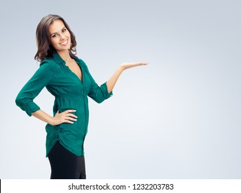 Portrait of beautiful woman in green confident clothing showing something or empty copyspace place for some slogan, text message, or product, against grey background. Business and advertising concept.
