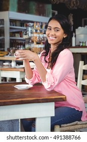 Portrait of beautiful woman having coffee in cafeteria